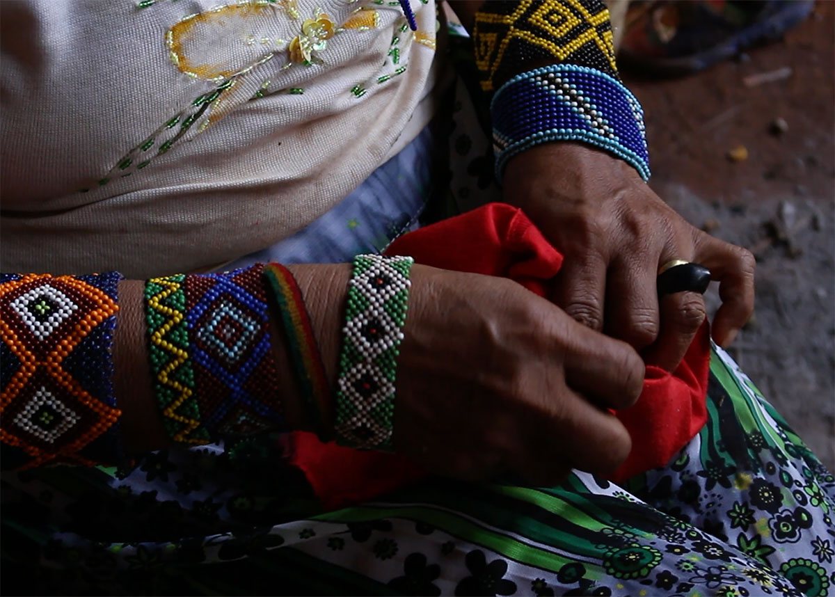 Closeup on a pair of hands holding a piece of red fabric. The person is adorned with several colorful beaded bracelets.