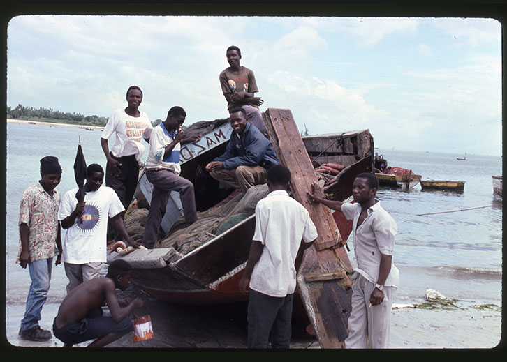 Archival photo of a group of men on and around a wooden boat washed ashore.