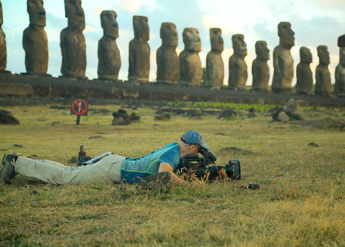 A person lays on their stomach on the ground with a film camera to their eye. In the background are several Moai statues of Easter Island.