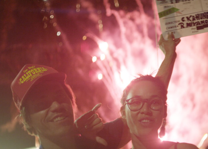 Two people smile, one holding a director's clapboard, with pink fireworks going off behind them.