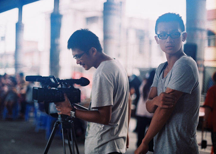 Two men outdoors, under a freeway overpass. One is smiling, looking into the viewfinder of a video camera.