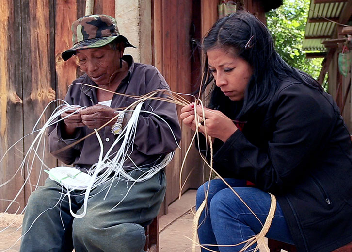 Two people sit outside, weaving some natural fibers by hand.