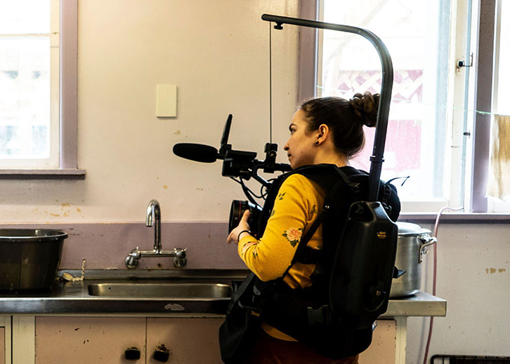 A woman with a camera rig strapped to her chest films in a kitchen.